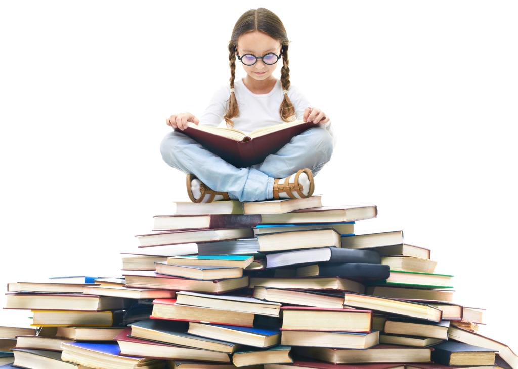 Portrait of girl with glasses and open book sitting on pile of books